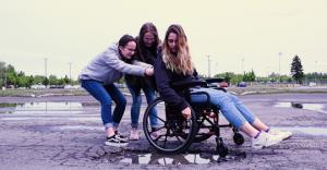 image de 3 jeunes filles, dont une est en fauteuil roulantnt